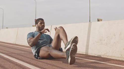 African-American Man Doing Crunches on Race Track