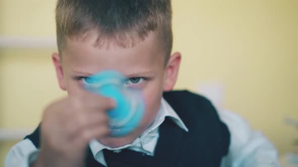 Funny Schoolkid Turns Blue Spinner on Blurred Background