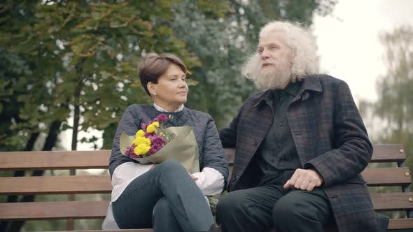 Positive Handsome Senior Man Talking with Woman Sitting on Bench in Autumn Park