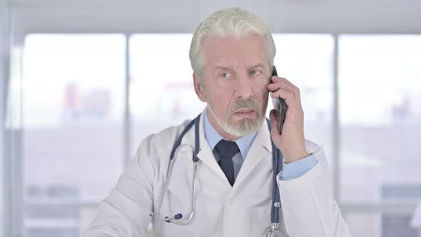 Portrait of Old Senior Doctor Talking on Smartphone in Clinic