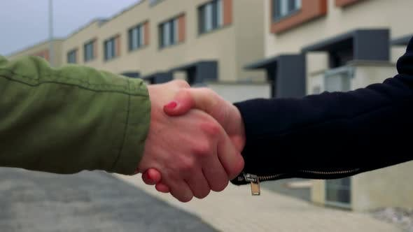 Thumbnail for A Male and a Female Hands Shake, a Street in the Background - Closeup