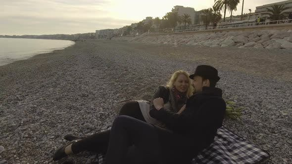Thumbnail for Young couple lying on beach and talking, woman kissing man, loving relationship