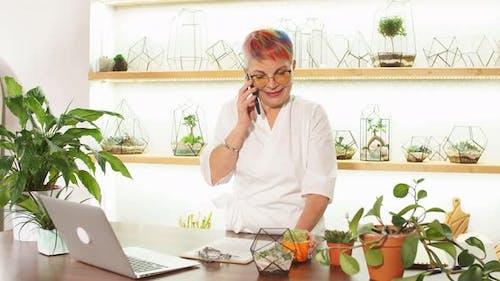 Senior Caucasian Florist Wearing Eyeglasses in Workplace Talking on Mobile Phone
