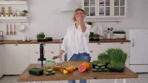 Young Woman Cuts a Kiwi to Make a Cocktail with Microgreens and Sprouted Wheat