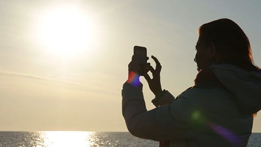 Thumbnail for Woman shooting on Smartphone Sunset