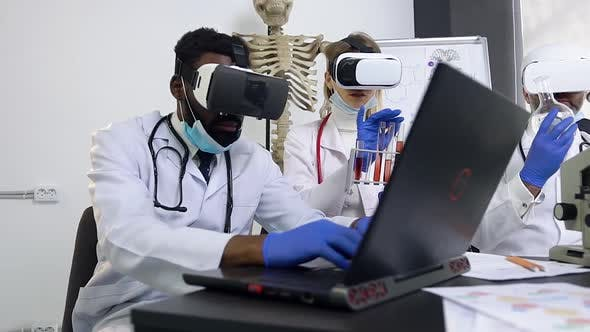 Medical Assistant in White Gown Working with Computer Using Augmented Reality Goggles