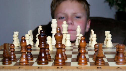 Little Boy Fascinated By The Game Of Chess