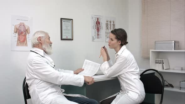 Cover Image for Medical Discussion of Electrocardiogram of Senior Doctor and Young Female Doctor