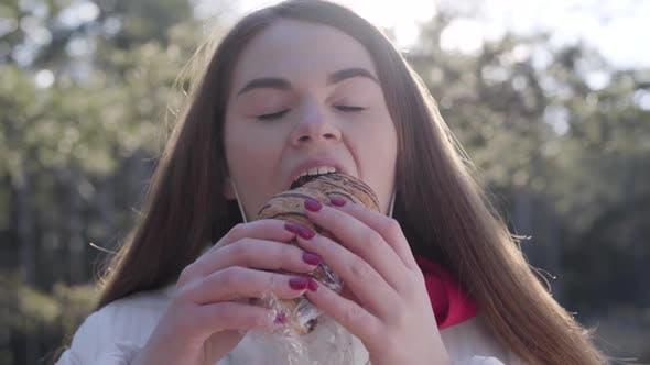 Thumbnail for Nahaufnahme von Brünette Mädchen Abnehmen Gesichtsmaske und Essen leckere Croissant im Freien. Junge Kaukasier