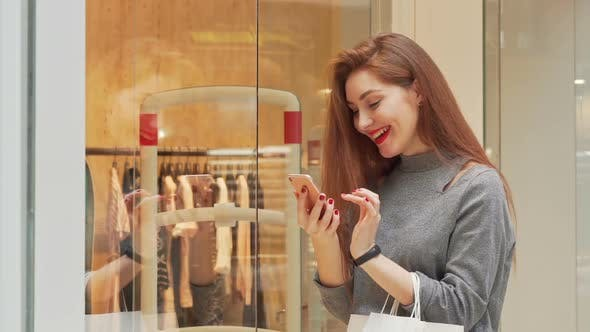 Thumbnail for Young Woman Laughing Using Smart Phone While Shopping at the Mall