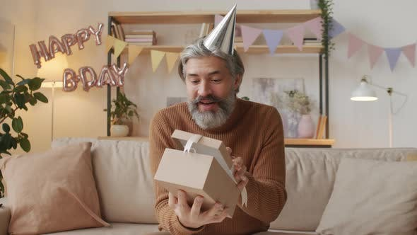 Thumbnail for Middle-Aged Man Opening Birthday Present