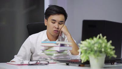 tired student sitting at the table with book and laptop