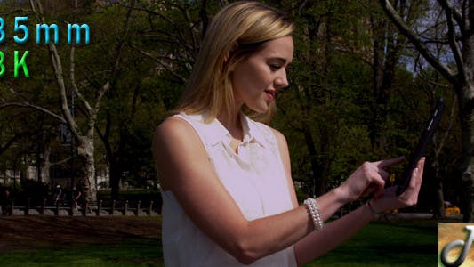Thumbnail for Woman In Central Park Using Digital Tablet