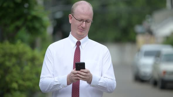 Thumbnail for Happy Mature Bald Businessman Thinking While Using Phone Outdoors