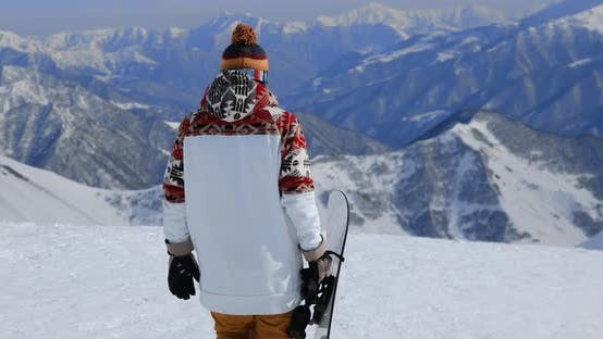 Thumbnail for Enthusiastic Snowboarder Holding His Snowboard While Walking at the Top of a Mountain