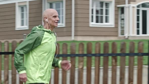 Thumbnail for Concentrated Senior Athlete Jogging with Earphones