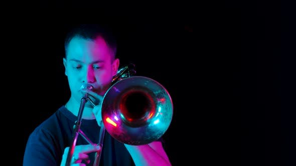 Thumbnail for Front View of a Musician Playing the Trombone in the Studio Against a Black Background in Neon Light