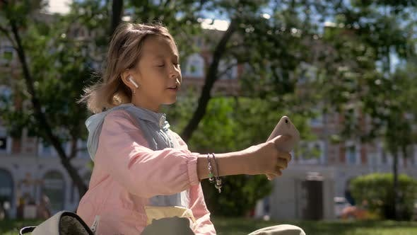 People, Children and Technology Concept - Girl with Laptop Computer and Smartphone Taking Selfie