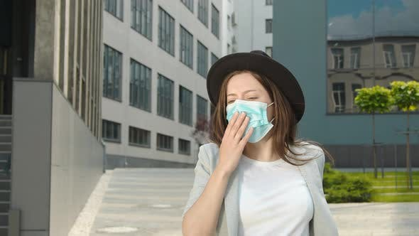 Thumbnail for A Woman in a Medical Mask Walking Down the Street and Coughing. A Woman with Signs of Illness Coughs