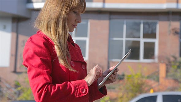 Thumbnail for Young Woman Uses Tablet Computer Outdoor