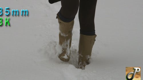 Woman Walking On Deep Snow