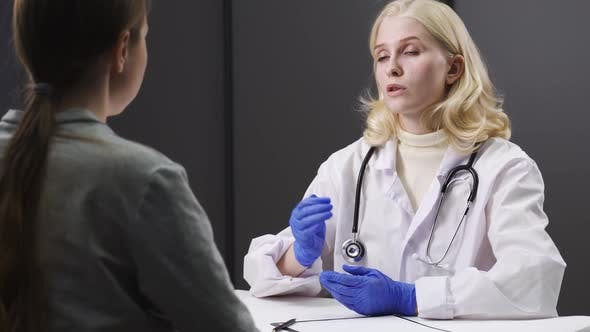 Young Female Doctor in White Medical Uniform Talk Discuss Results or Symptoms with Female Patient