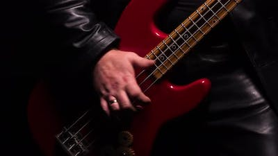Detailed Macro Shot of Male Hands Playing Red Bass Guitar