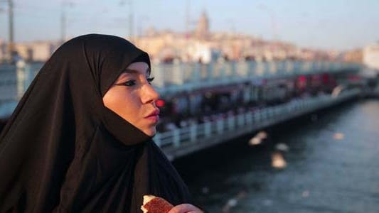Woman With Chador Eating Simit, Turkish Bagel