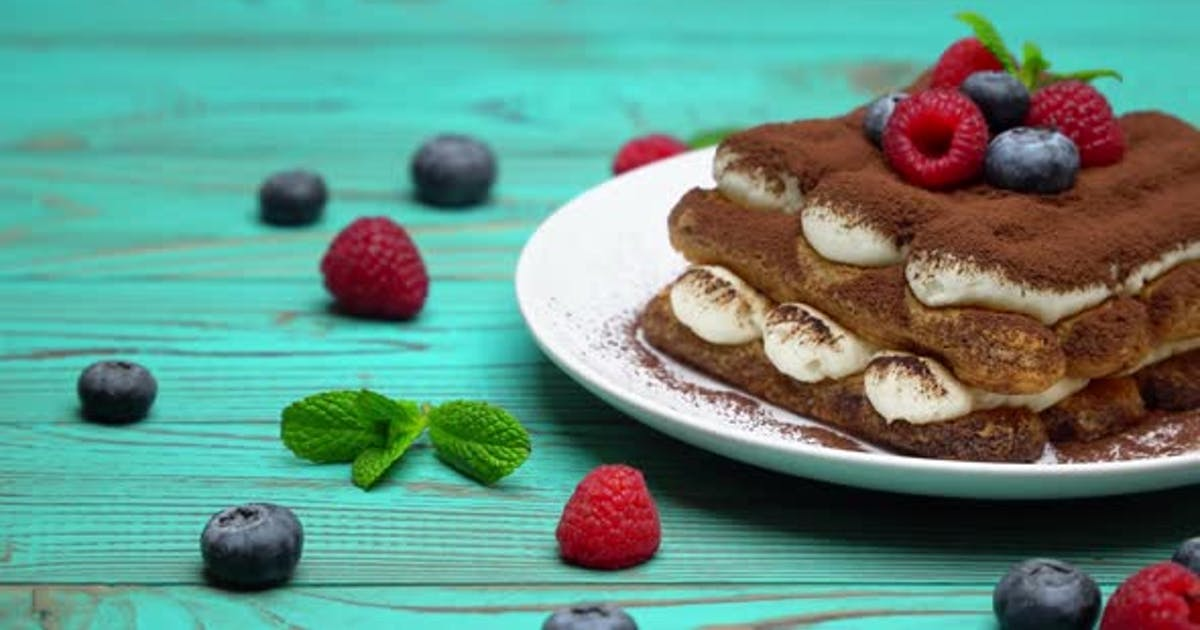 Portion of Classic Tiramisu Dessert with Raspberries and Blueberries on Wooden Background