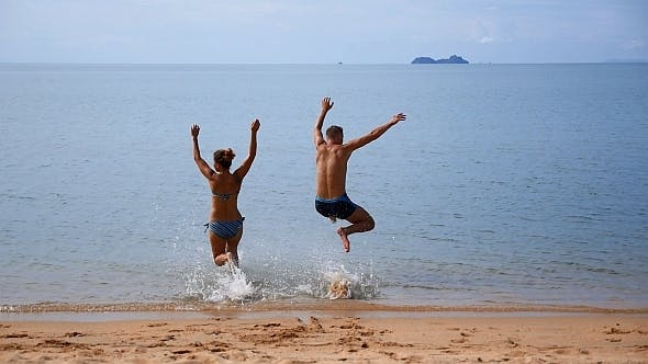 Thumbnail for Couple on Vacation Jumping in the Sea