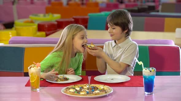 Thumbnail for Brother and Sister Enjoying Chocolate Pizza at Children's Restaurant.
