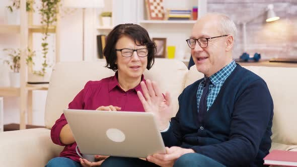 Elderly Age Couple Sitting on Sofa Holding Laptop During a Video Call.