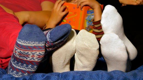 Thumbnail for Familys Feet In Socks Over The Covers