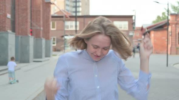 Woman Dancing in Joy While Walking in Street