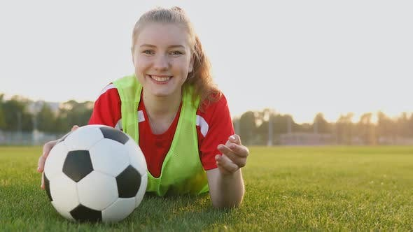 Portrait of a smiling teen girl football player lying on field with soccer ball