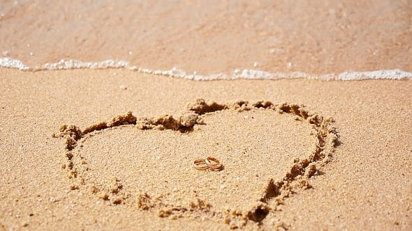 Golden Rings in Heart Symbol in Sea Waves