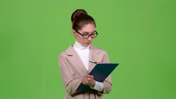 Thumbnail for Manager füllt den Fragebogen mit einem Stift auf einem Papiertablett aus. Grüner Bildschirm