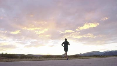 Man Jogging on Countryside Road at Sunset for Health and Wellness