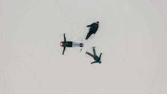 Thumbnail for Aerial Top View of Happy Three People Having Fun During Winter Vacation Playing with Snow Doing