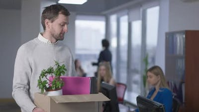 Portrait of Jobless Frustrated Caucasian Man Posing with Box in Office