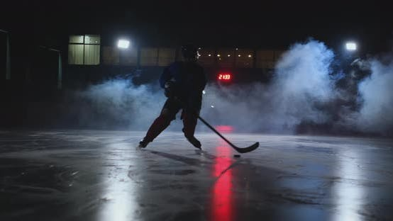 Thumbnail for Male Hockey Player with a Puck on the Ice Arena Shows Dribbling Moving Directly Into the Camera and