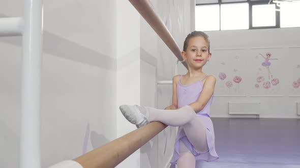 Thumbnail for Beautiful Little Ballerina Girl Stretching on Ballet Bar at Dance School