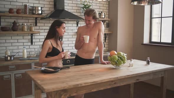 Thumbnail for Smilling Young Couple in the Beautiful Loft Kitchen. Guy and a Girl in Underwear Are Drinking Their