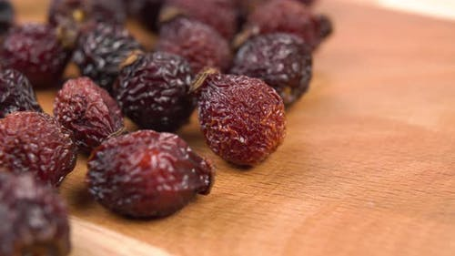 Dried wild rose hips. Macro. Healing natural fruits on a wooden board