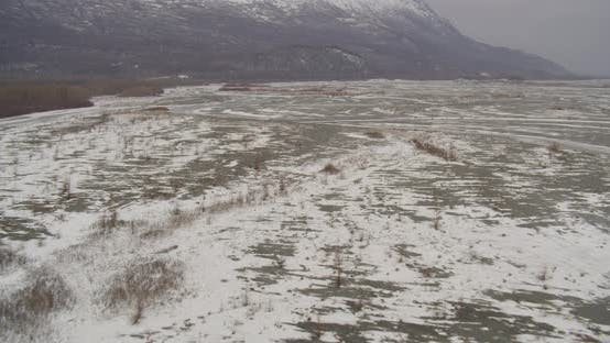 Aerial helicopter wide shot, tilt up past Alaskan mountain range, over valley to showcase snowy slop