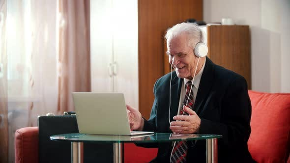 Thumbnail for Elderly Grandfather - Old Grandfather in Headphones Smiling and Looking at Laptop Screen in His