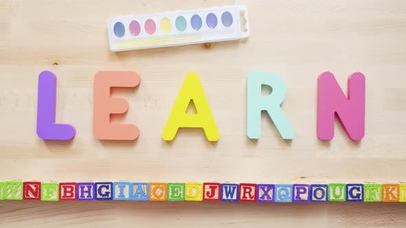 Thumbnail for Word LEARN from multicolor wooden letters on wooden table.