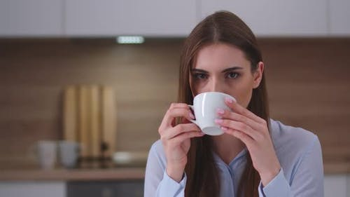 Young Female Sitting in the Kitchen and Drinking Coffee, Looks at the Camera, Portrait, Day Off