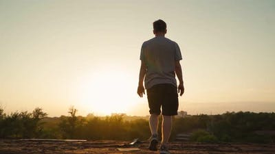Happy man walks to the edge of the roof and raises his hands to the sides. Motivational video