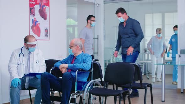 Thumbnail for Invalid Old Man with Face Mask Discussing with Doctor in Hospital Waiting Area